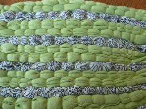 Premier prototype de tissage en lirette réalisé sur un carton transformé en métier à tisser, à partir d'un débardeur blanc à motif, d'un col roulé vert et de fils de couture