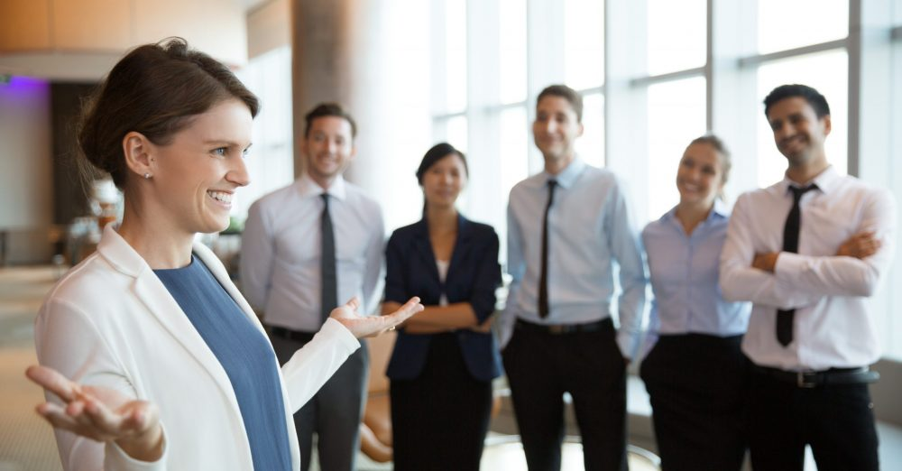 Portrait of smiling businesswoman with open hands gesture standing in office hall, her business team on background