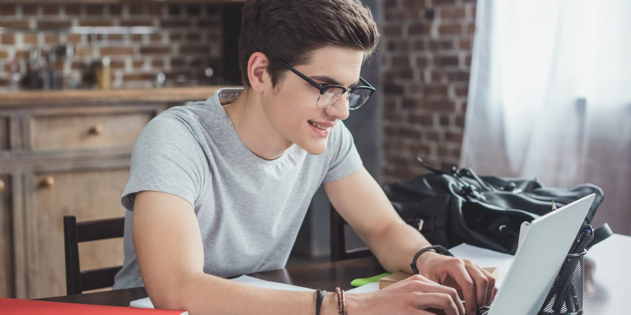smiling student doing homework and typing on laptop